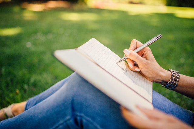 woman journalling outdoors. Self-Discovery.