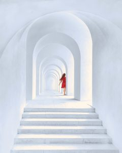 Woman walking down white hallway