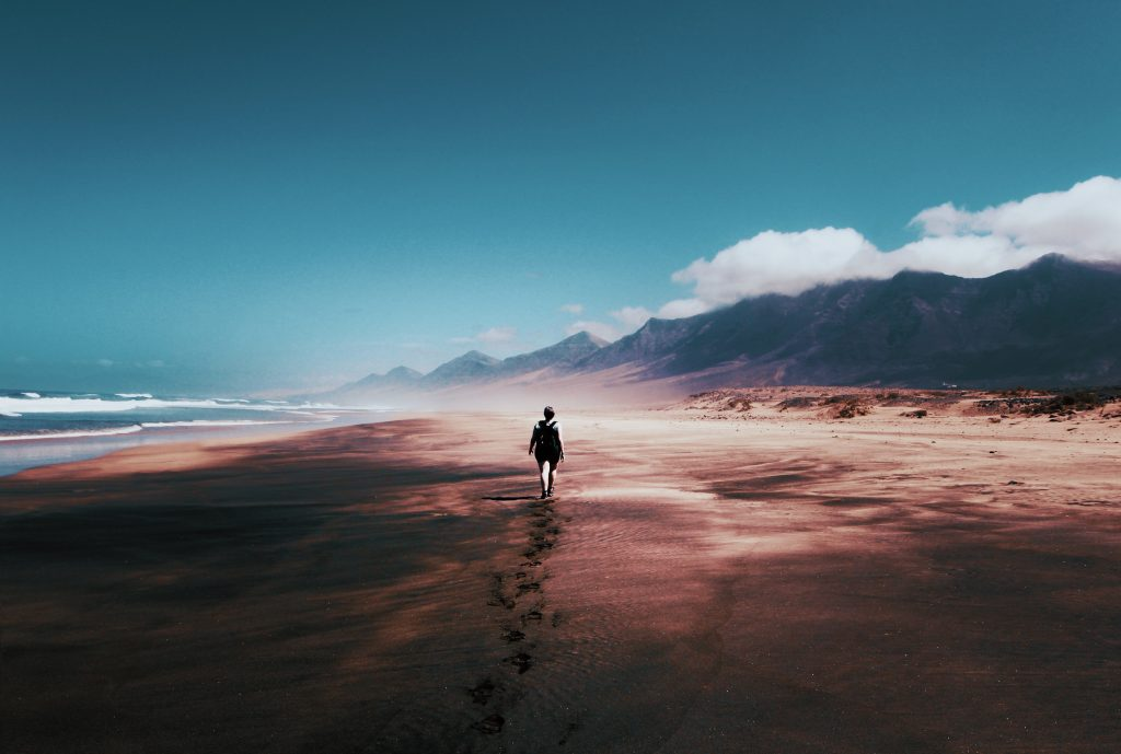 Woman walking away between the sea and mountains