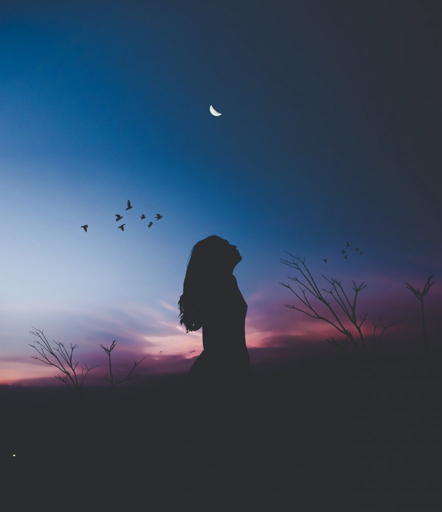 Woman backlit against night sky
