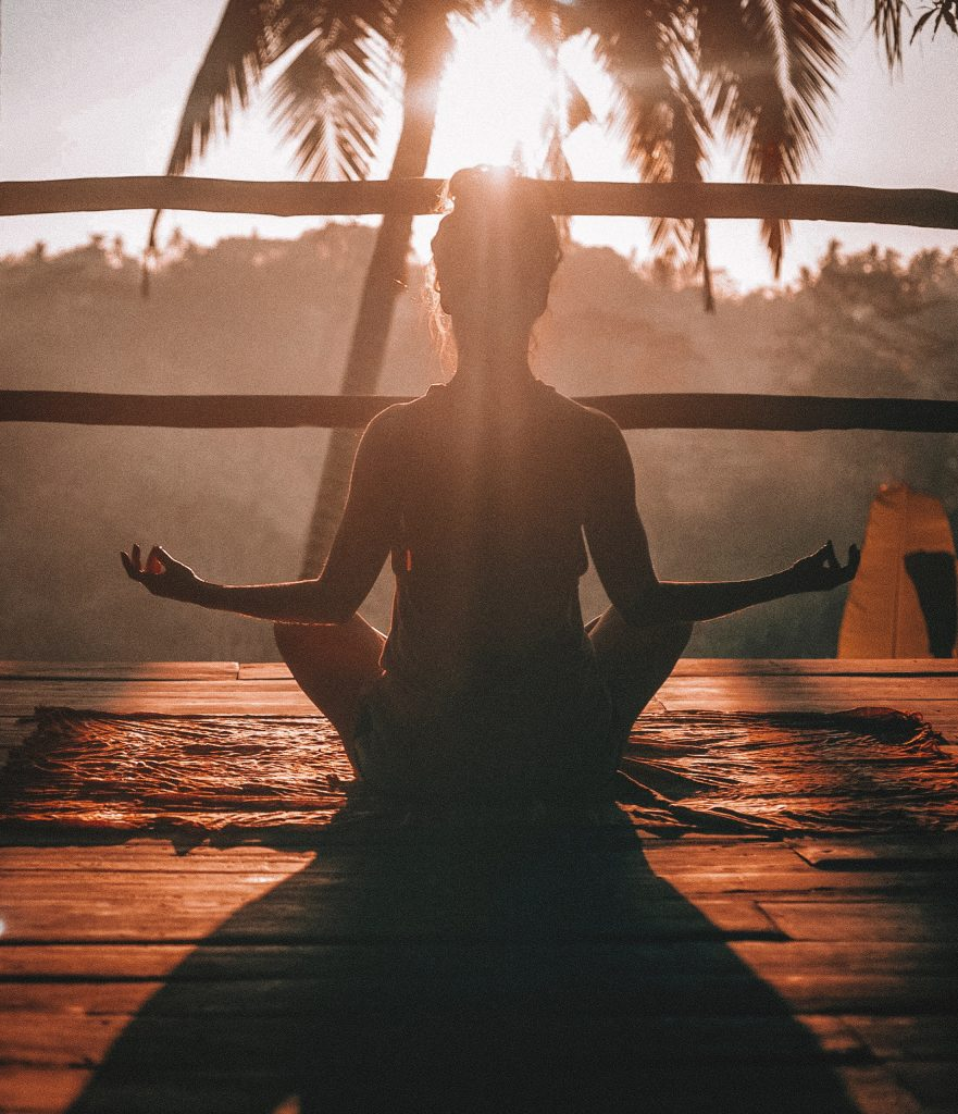 Woman meditating at sunrise